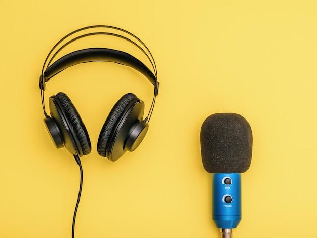 Cuffie nere e microfono blu su sfondo giallo. attrezzature per la registrazione, la comunicazione e l'ascolto di musica. Foto Premium