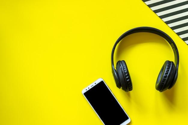 Cuffie nere e un telefono su uno sfondo giallo. concetto minimale. design. disteso. Foto Premium