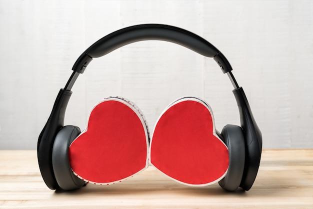 Cuffie stereo senza fili e due scatole a forma di cuore. ascolta il tuo cuore Foto Premium