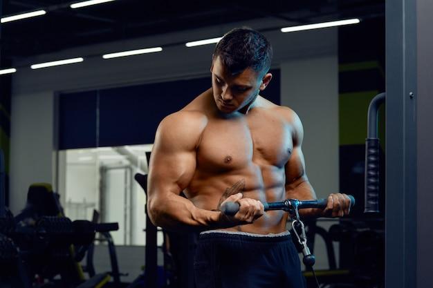 Culturista muscolare che fa esercizi sulla macchina del crossover via cavo in palestra l'uomo forte atletico mostra il corpo, i muscoli addominali, i bicipiti e i tricipiti. Foto Premium