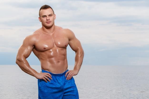 Culturista sexy sulla spiaggia Foto Gratuite