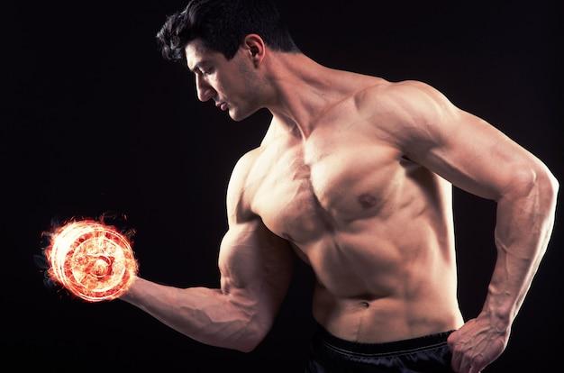 Culturista strappato muscolare con manubri in fiamme Foto Premium