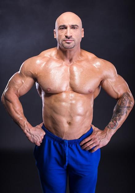 Culturista uomo sta dimostrando la sua muscolatura perfetta Foto Premium