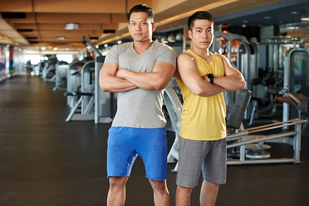 Culturisti in piedi spalla a spalla in palestra mostrando i loro muscoli Foto Gratuite