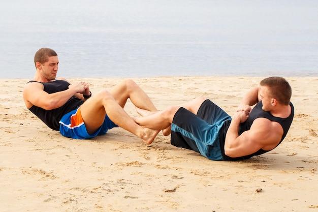 Culturisti sulla spiaggia Foto Gratuite