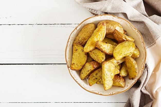 Cunei della patata al forno con aglio su un fondo bianco. Foto Premium