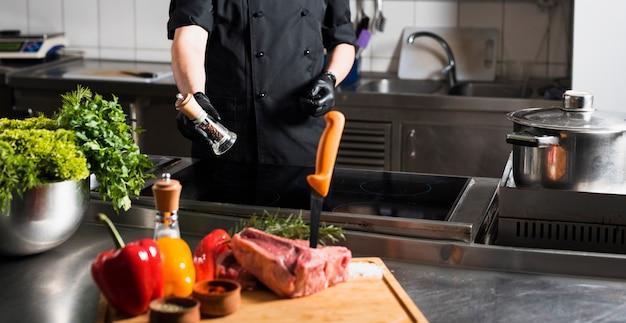 Cuocere in piedi con lo shaker al tavolo Foto Gratuite