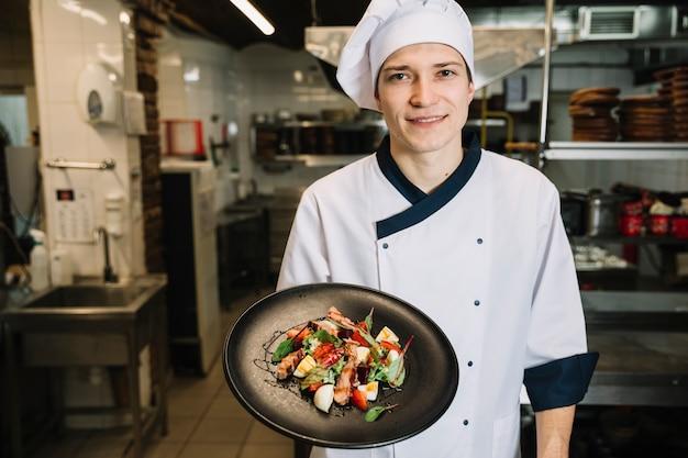 Cuocere mostrando insalata con carne sul piatto Foto Gratuite