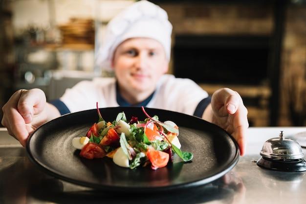 Cuocere tenendo il piatto con insalata vicino campana di servizio Foto Gratuite