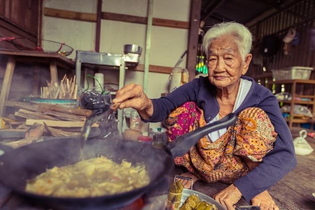 Cuoco asiatico senior del cuoco unico della donna nella cucina, tradizionale in tailandia Foto Premium