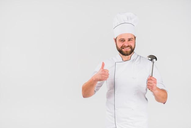 Cuoco del cuoco unico che gesturing pollice in su con la siviera Foto Gratuite