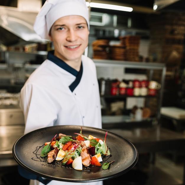 Cuoco felice che mostra insalata con carne sul piatto Foto Gratuite