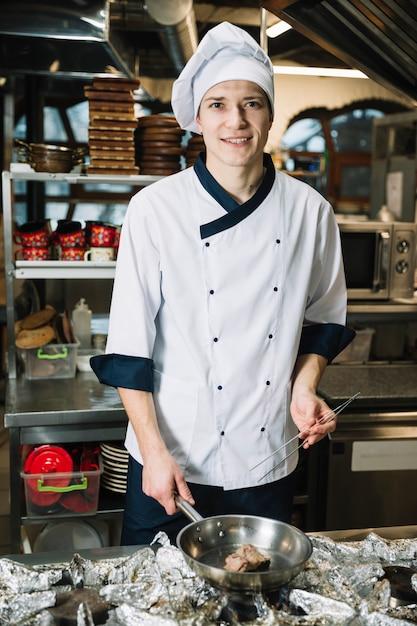 Cuoco gioioso friggere carne in padella sul fornello Foto Gratuite