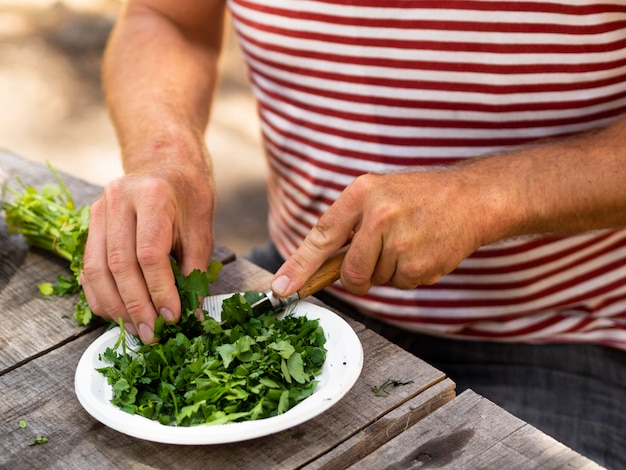 Cuoco irriconoscibile che taglia sedano per insalata Foto Gratuite