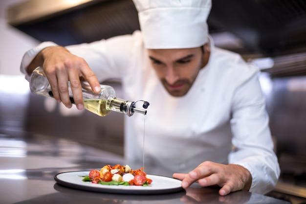 Cuoco unico bello che versa olio d'oliva sul pasto Foto Premium