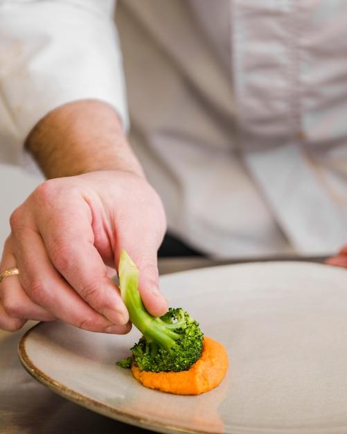 Cuoco unico che immerge broccoli in salsa Foto Gratuite