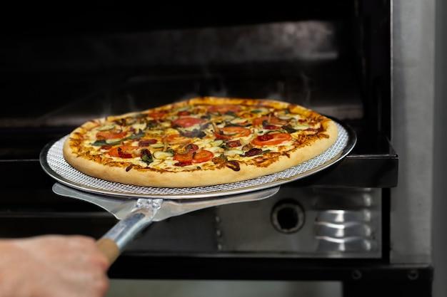 Cuoco unico che mette lo strato di cottura della pizza in forno al ristorante con l'attrezzatura della pala della pizza. Foto Premium