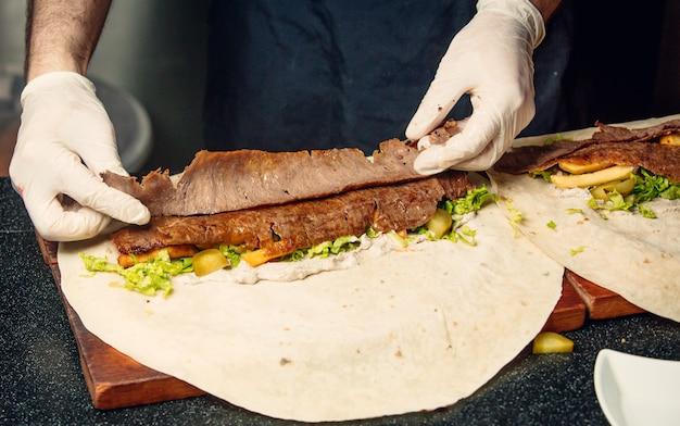 Cuoco unico che prepara doner di lavash con carne e verdure. Foto Gratuite