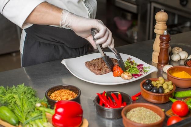 Cuoco unico che prepara la bistecca di manzo per il servizio con insalata e verdure grigliate Foto Gratuite