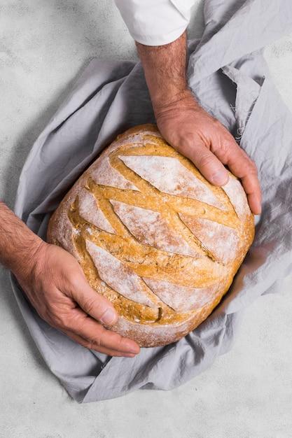 Cuoco unico che si tiene per mano sul pane rotondo Foto Gratuite