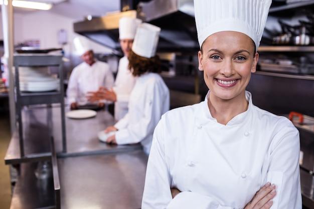 Cuoco unico felice che sta nella cucina commerciale in un ristorante Foto Premium