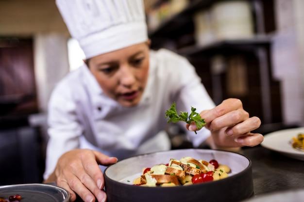 Cuoco unico femminile che guarnisce i dessert deliziosi in un piatto Foto Premium