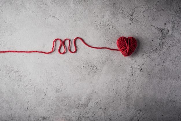 Cuore di filato rosso a forma di sullo sfondo del muro Foto Gratuite