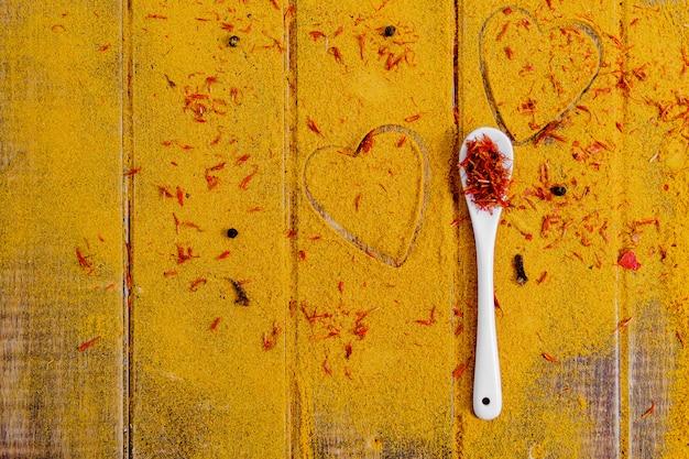 Cuore di spezie e condimenti. cucchiaio bianco con zafferano su sfondo di curry. Foto Premium