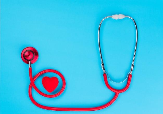 Cuore e stetoscopio rossi sopra sul blu. Foto Premium