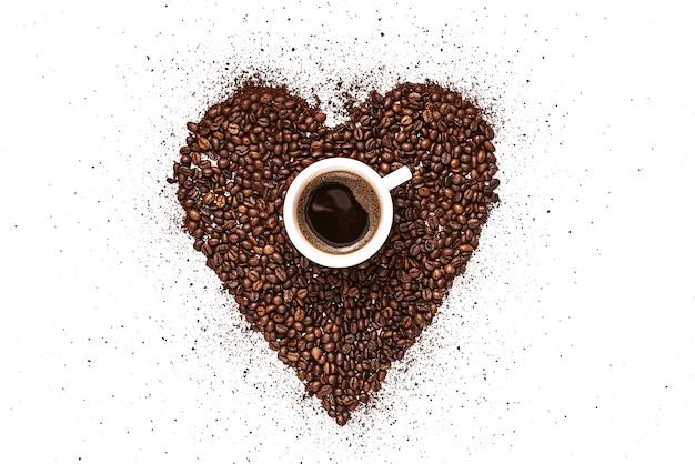 Cuore fatto di chicchi di caffè tostato e caffè macinato su un piatto bianco e una tazza di caffè appena preparato Foto Premium