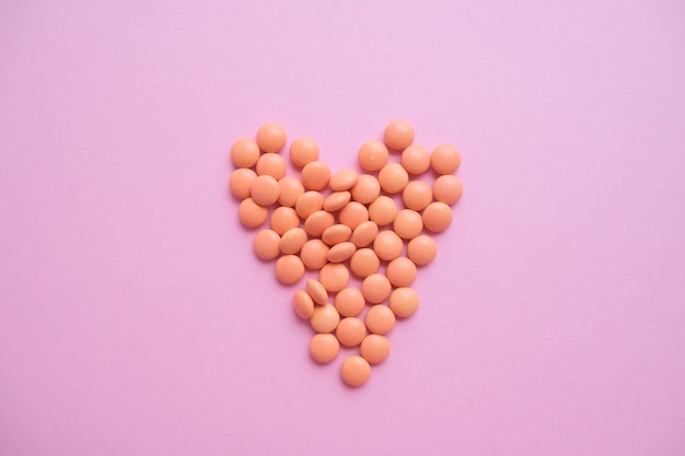 Cuore fatto di compresse arancioni dalla bottiglia di vetro. epidemia, antidolorifici, assistenza sanitaria, pillole di trattamento e concetto di abuso di droghe. vista dall'alto. flatlay. Foto Premium