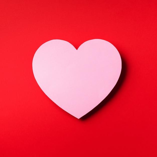 Cuore rosa tagliata da carta su sfondo rosso con spazio di copia. Foto Premium