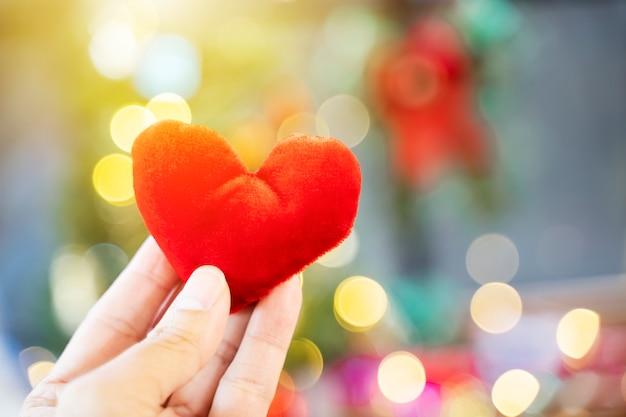 Cuore rosso a portata di mano con sfondo chiaro offuscata. amore, matrimonio e concetto di san valentino. Foto Premium