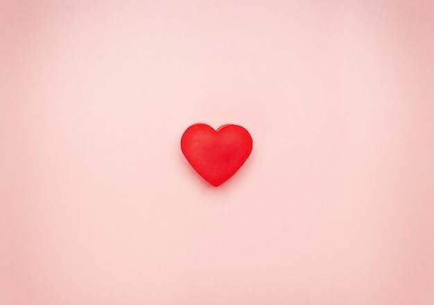 Cuore rosso al centro di uno sfondo rosa Foto Premium