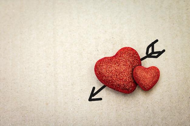 Cuore rosso con freccia di cupido su cartone. san valentino. Foto Premium
