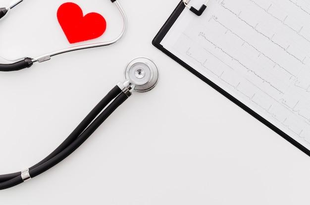 Cuore rosso con lo stetoscopio vicino al rapporto medico del ecg su fondo bianco Foto Gratuite