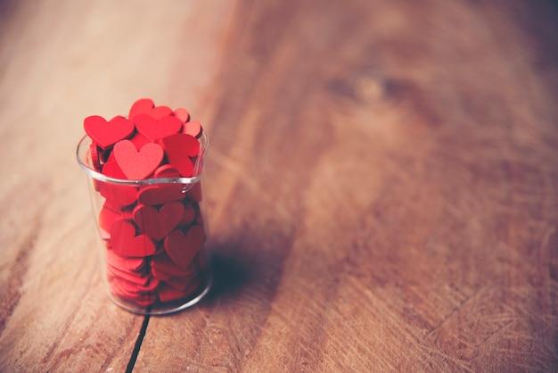 Cuore rosso di giorno di biglietti di s. valentino su vecchio legno. carta vacanze con spazio di copia Foto Premium