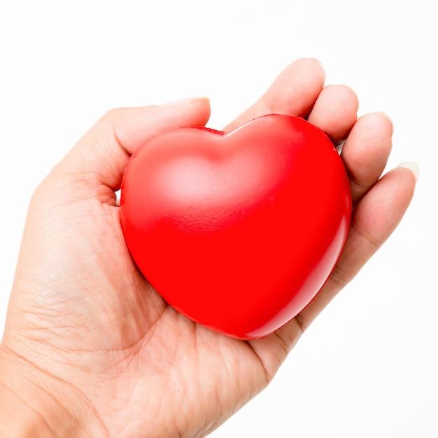 Cuore rosso in mano isolato su sfondo bianco illuminazione da studio. Foto Premium