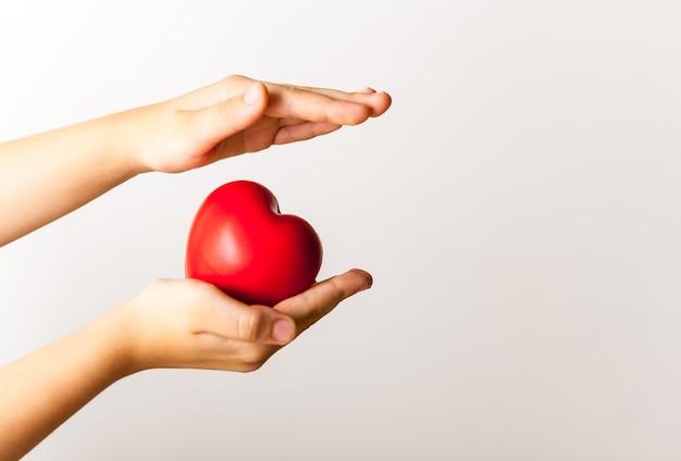 Cuore rosso nelle mani del bambino su sfondo chiaro Foto Premium