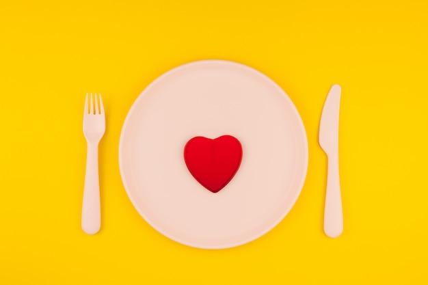 Cuore rosso sul tavolo del servizio. concetto romantico Foto Premium