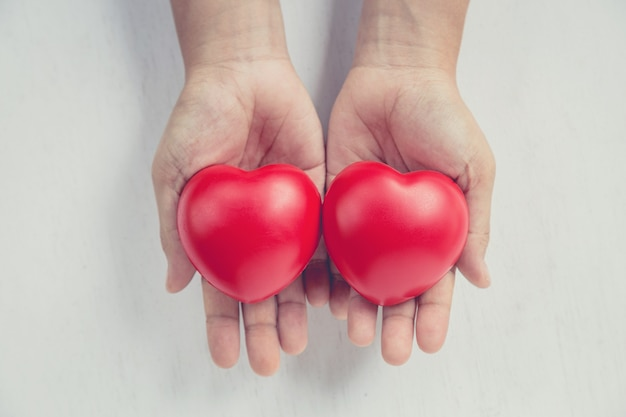 Cuore rosso sulla mano della ragazza Foto Premium