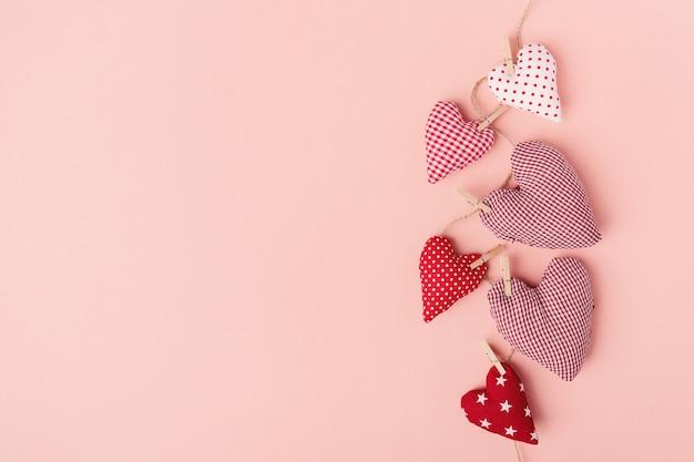 Cuori del giorno di san valentino del tessuto sul rosa Foto Gratuite