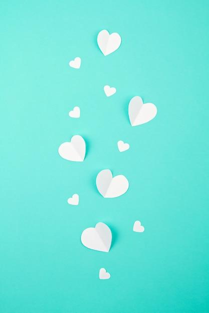 Cuori di carta bianca su sfondo turchese. sainte valentine, festa della mamma, biglietti d'auguri di compleanno, invito, celebrazione concetto Foto Premium