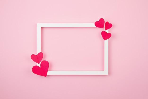Cuori di carta e cornice bianca su sfondo rosa pastello. Foto Premium