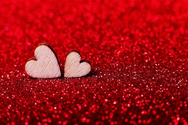 Cuori di legno su sfondo rosso brillante brillante per una decorazione festiva Foto Premium