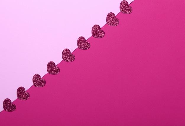 Cuori glitter rosso su sfondo rosa e rosso. romantico, concetto di san valentino. vista dall'alto. Foto Premium