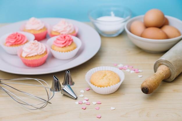 Cupcake decorativo con ingredienti; frusta; cospargere; mattarello e ugelli sulla scrivania in legno Foto Gratuite