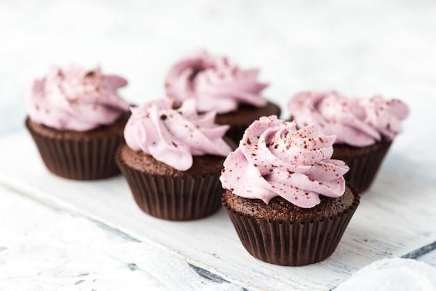 Cupcakes al cacao decorati con crema di bacche e cioccolato Foto Premium