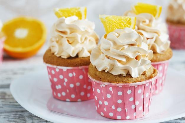 Cupcakes alla vaniglia con un tappo di crema su tablein in legno bianco Foto Premium