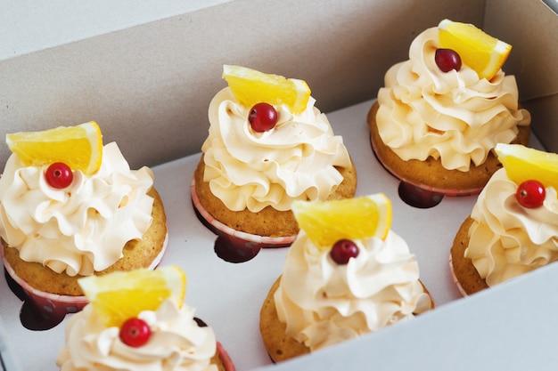 Cupcakes alla vaniglia con un tappo di crema sul tavolo di legno bianco nella scatola Foto Premium